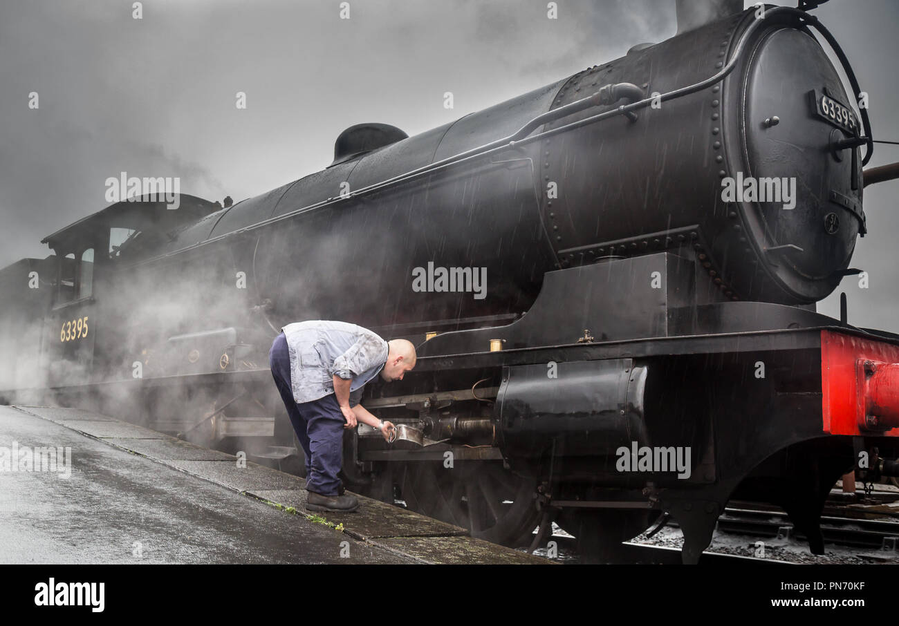 Kidderminster, UK. 20th September, 2018. UK weather: staff at Severn Valley Railway soldier on even though the rain continues. Persistent rain doesn't dampen the spirits of staff or travellers as visiting 63395 vintage steam locomotive receives an oil service at the Kidderminster station. It throws out plumes of steam into the damp air on its early morning run for the beginning of the SVR Autumn Steam Gala. Credit: Lee Hudson/Alamy Live News - Stock Image