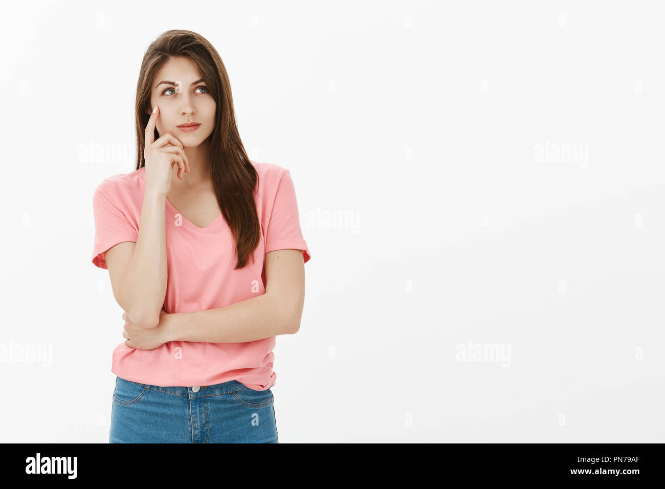 Determined smart attractive female student in pink t-shirt, holding index finger on temple and smiling while gazing at upper right corner, dreaming or making up ideas about future summer vacation Stock Photo