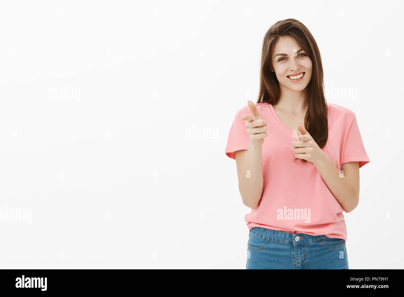 d3b4dd87f Girl making finger gun gesture to greet friend. Positive relaxed attractive  woman in pink t