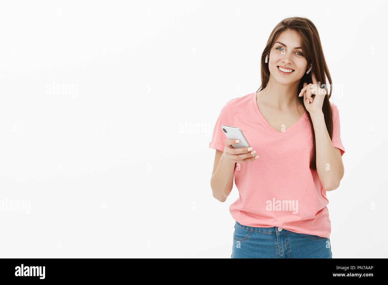 Hi how can I help you. Good-looking friendly and happy female office manager in pink t-shirt smiling broadly while touching wireless earphone in ear and holding smartphone, calling customer Stock Photo