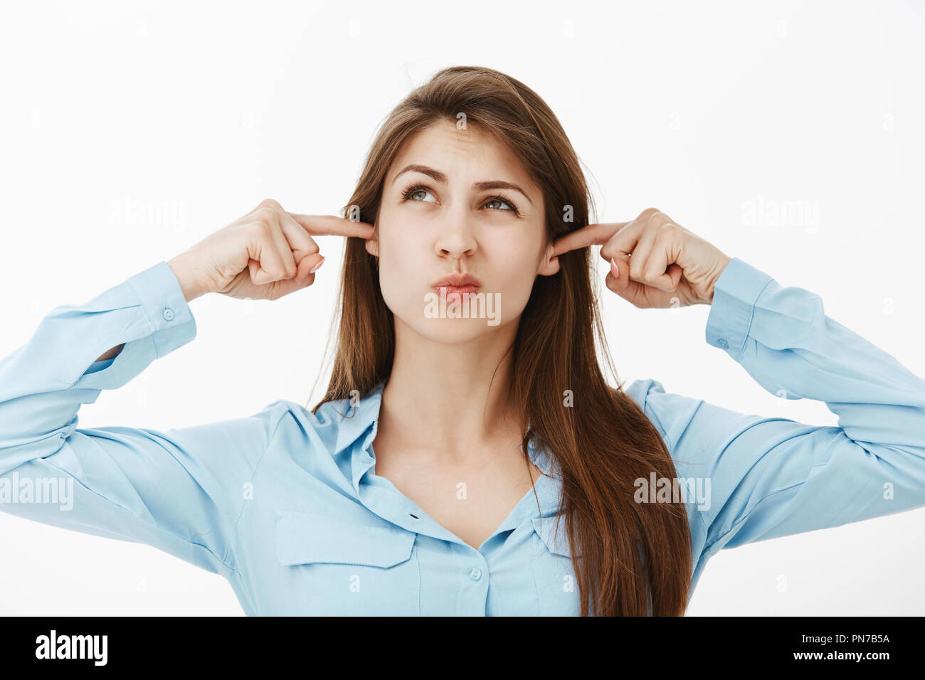 Displeased funny european girl in blue blouse, frowning, covering ears with index finger, looking up with folded lips, being displeased and annoyed, disturbed with loud noise from upstairs - Stock Image