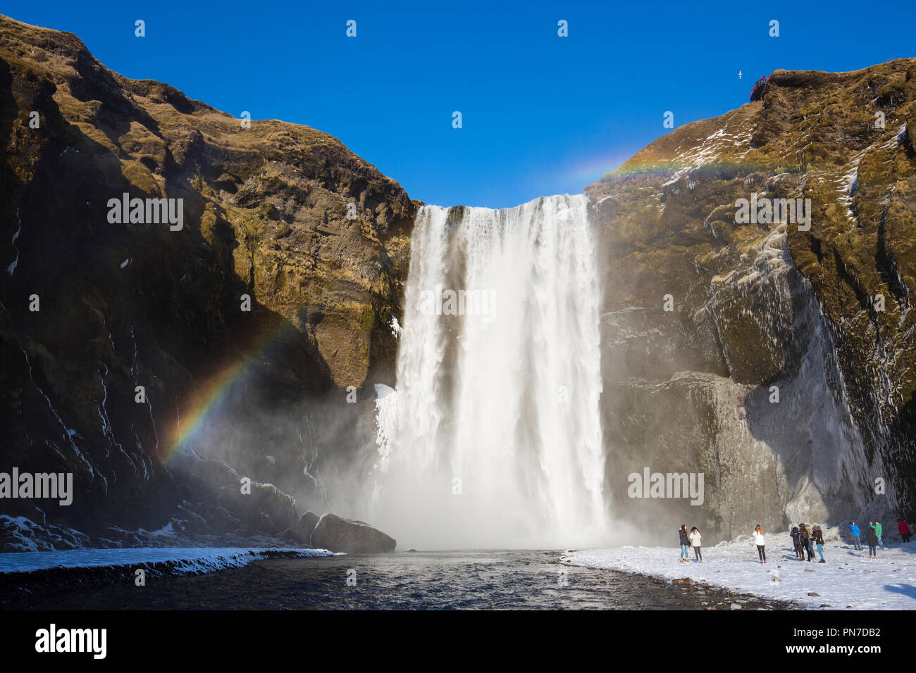 Tourists and rainbow at spectacular Skogar waterfall - Skogarfoss - in South Iceland with gushing glacial melting waters - Stock Image