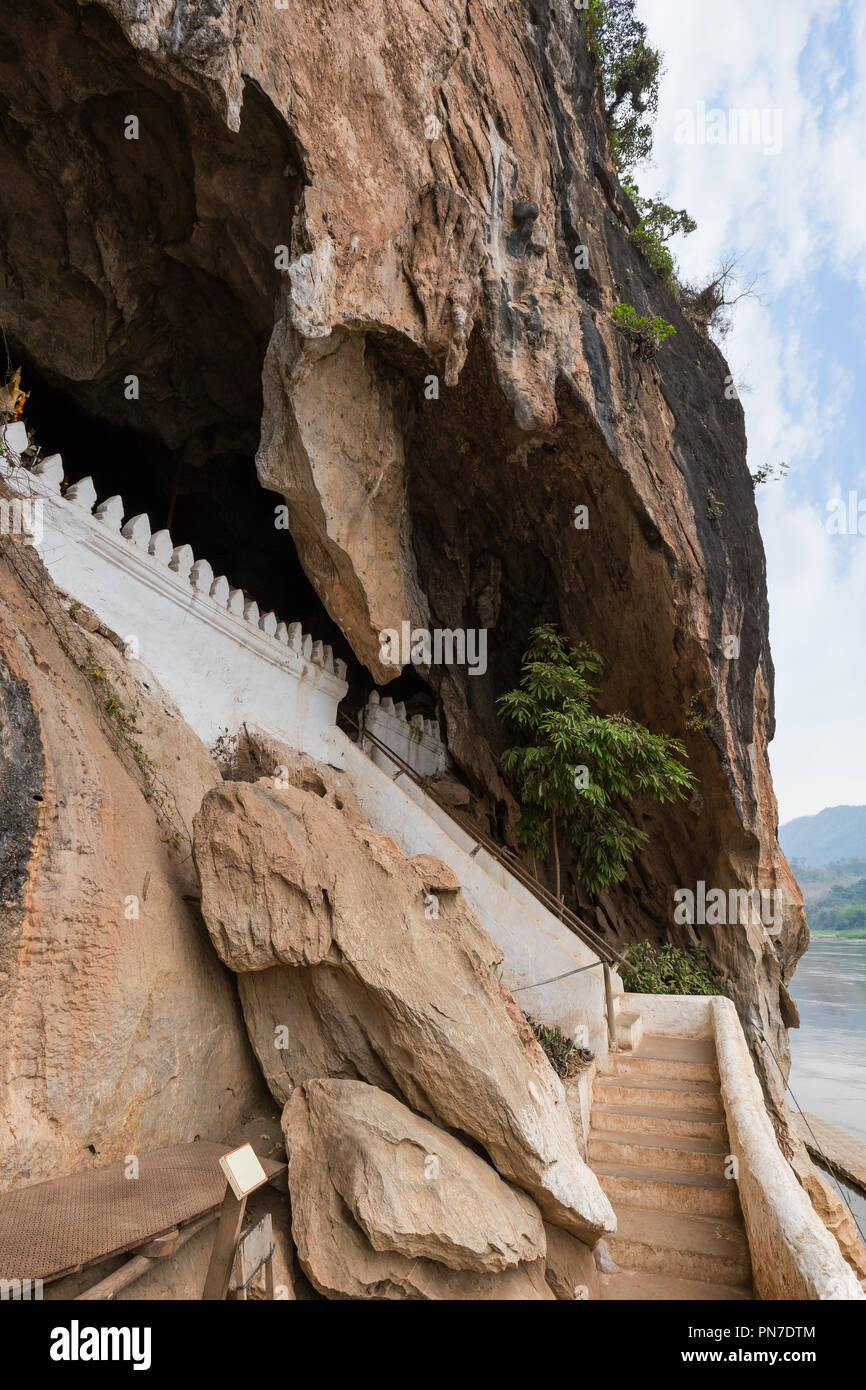Limestone cliff and stairs at the entrance to the Pak Ou Caves near Luang Prabang in Laos. - Stock Image