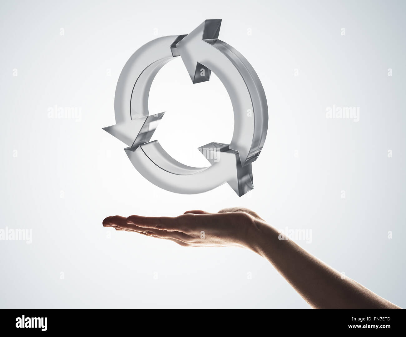 Concept of reuse and recycle presented by glass icon in palm - Stock Image