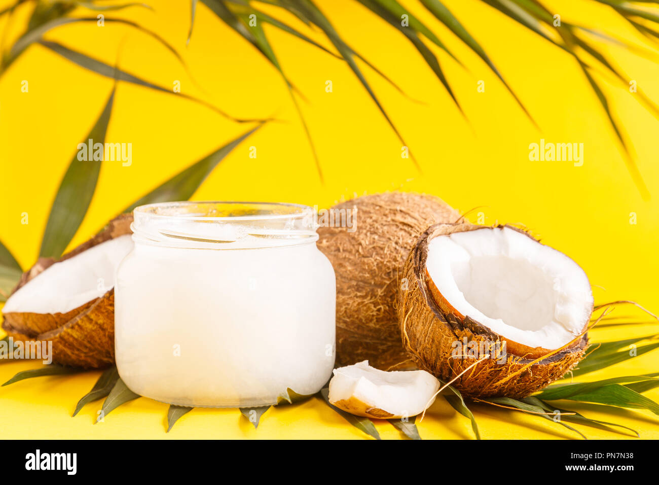 Coconut oil and coconuts on a bright pastel background, selective focus. Stock Photo