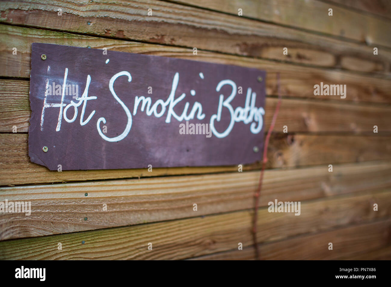 A slate sign that reads 'Hot Smokin Baths' - Stock Image