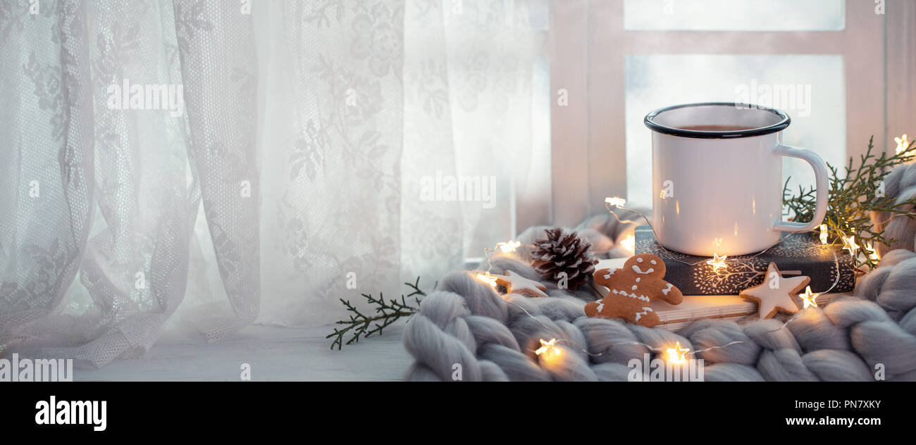 Cup of coffee with Christmas lights near window - Stock Image