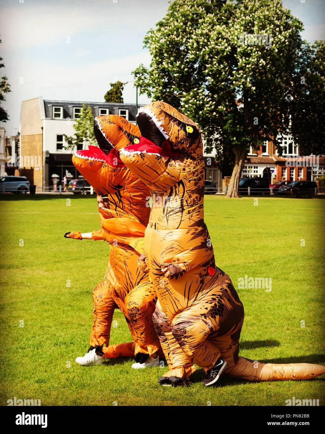 Two people wearing inflatable dinosaur costumes ( T Rex ) for fancy dress walk across Twickenham Green, UK - Stock Image