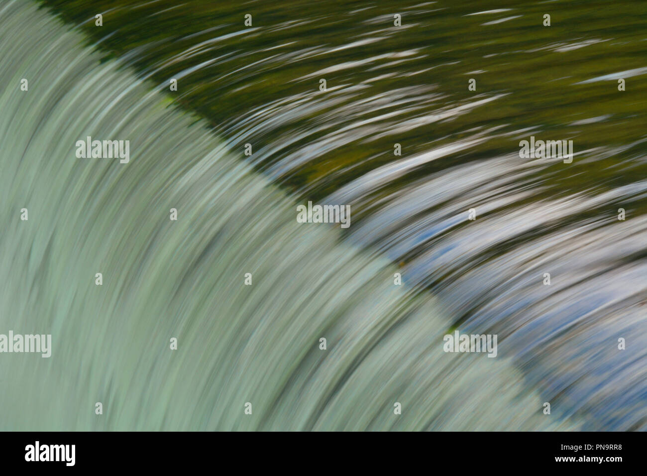 Smooth water flowing over the edge of a small falls in central Munich - Stock Image