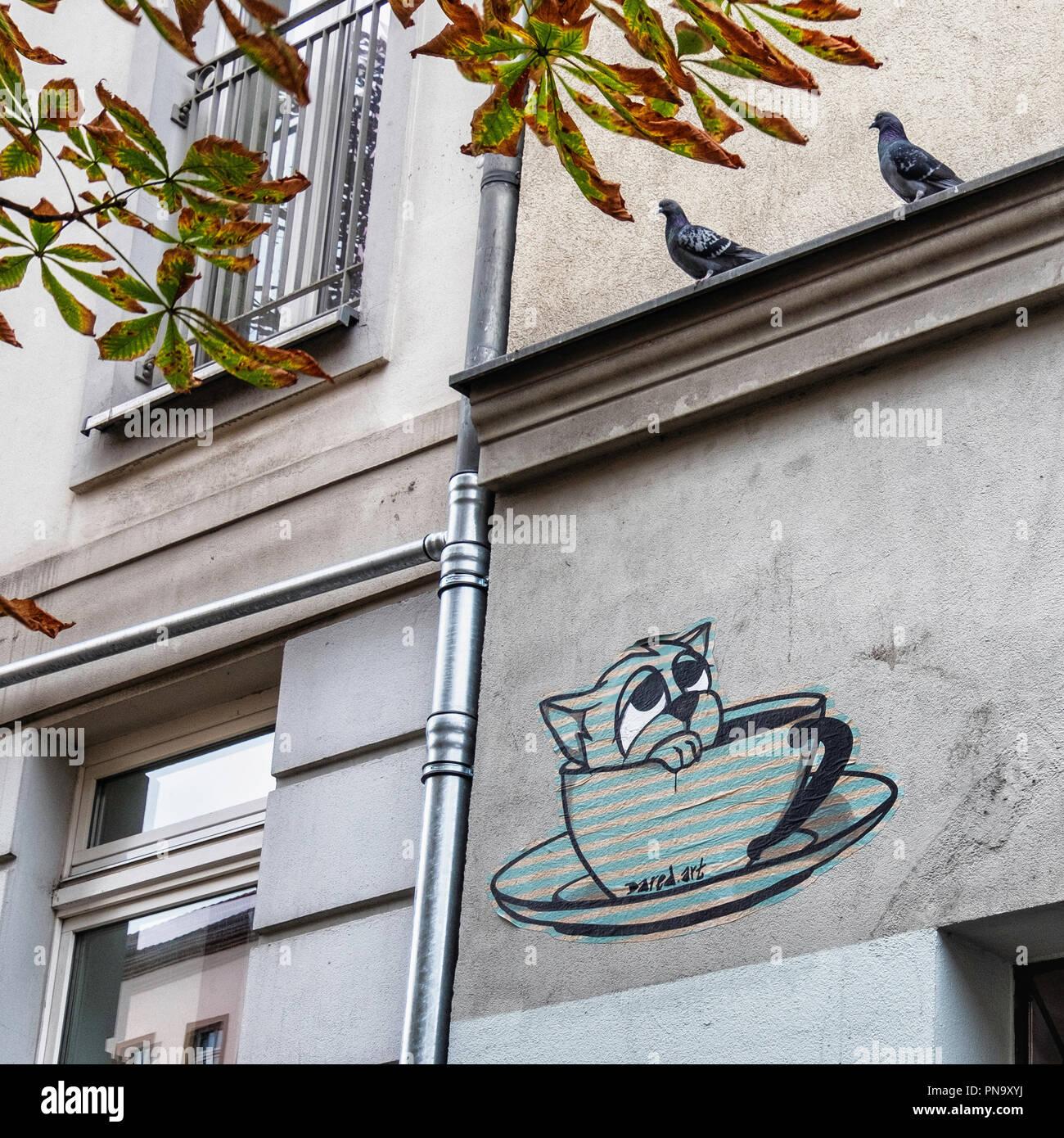 Berlin, Prenzlauer Berg. Urban street scene. Apartment building, two pigeons, diseased chestnut tree and street art paste-up by Dared - Stock Image