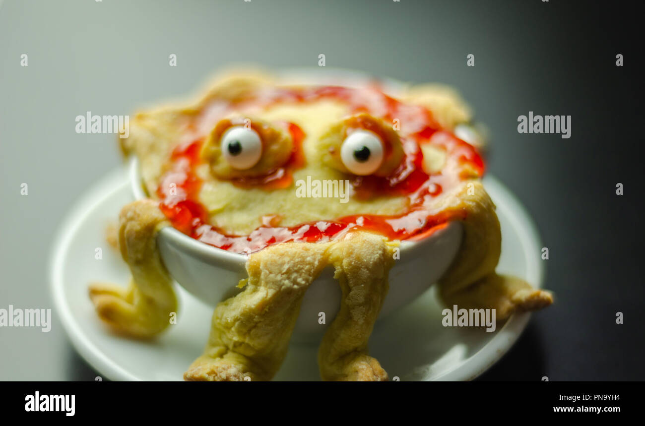 cake baked in the shape of a monster in a ceramic bowl, sweet for Halloween, scary food - Stock Image