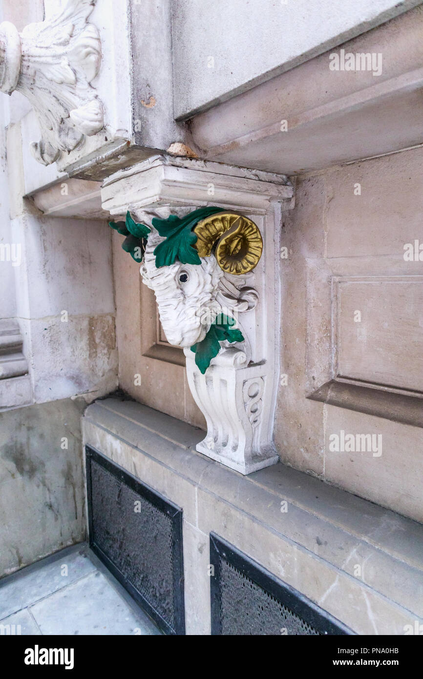 Architectural detail: stucco work ram's head with gilded horns on a building in St Swithin's Lane and Cannon Street in the City of London EC4 Stock Photo
