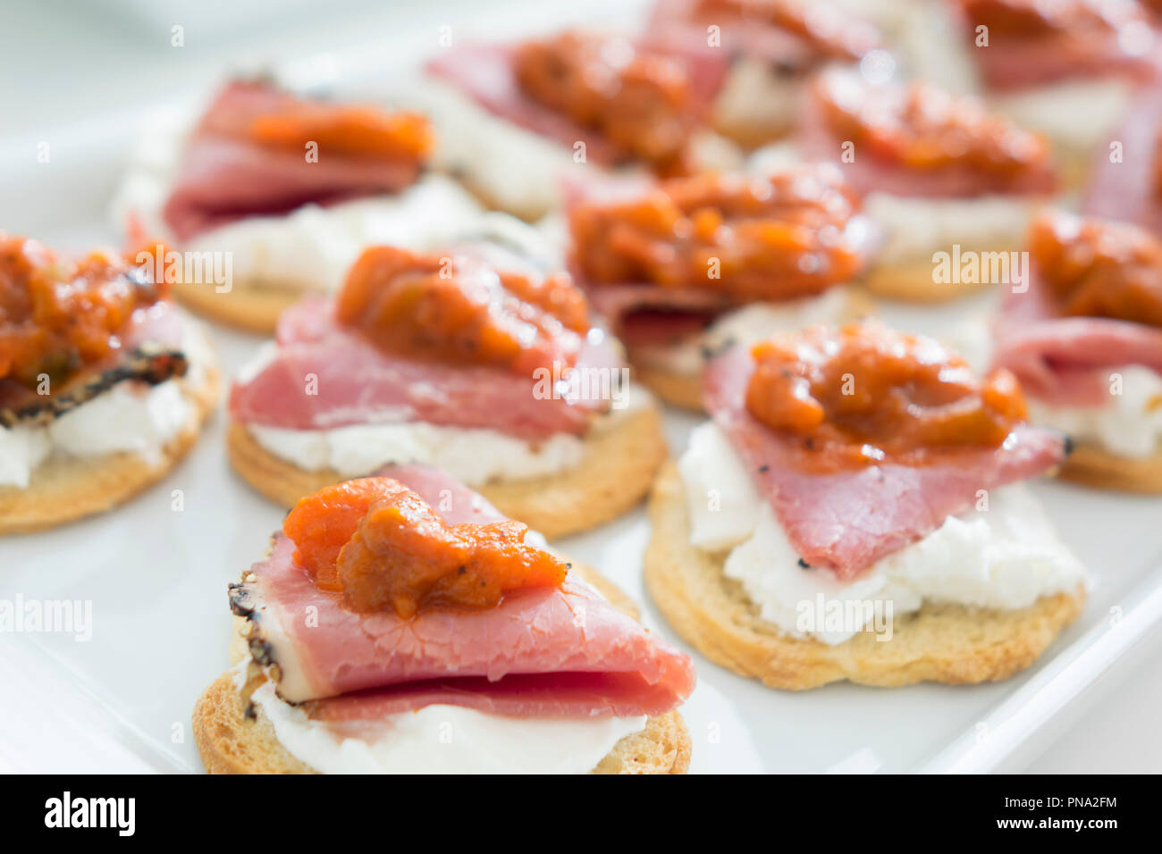 canape with smoked meat cheese and tomato sauce stock image - Mini Canape