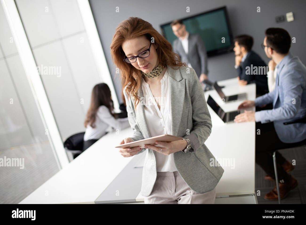 Business colleagues in conference meeting room during presentation - Stock Image