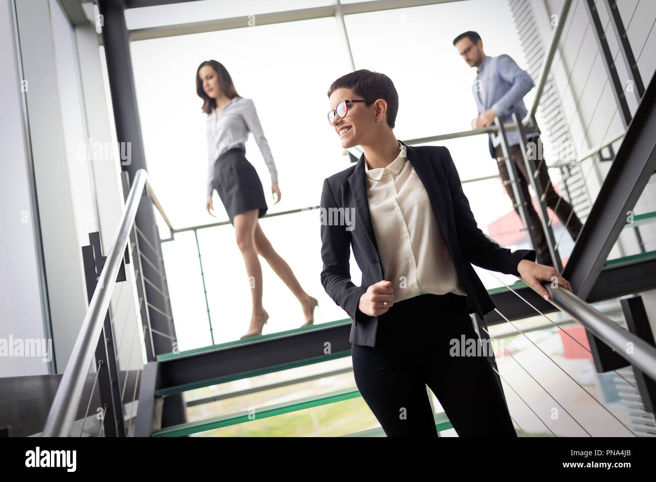 Confident business partners walking down in office building and talking - Stock Image