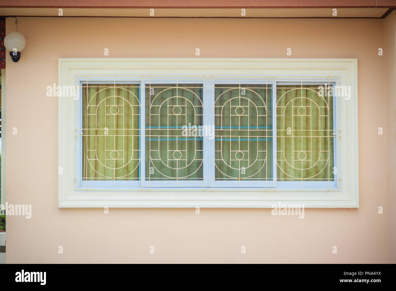 Window with wrought iron to prevent theft. Newly built house with window burglar bars and can see the decorated curtain through the window glass. Stock Photo