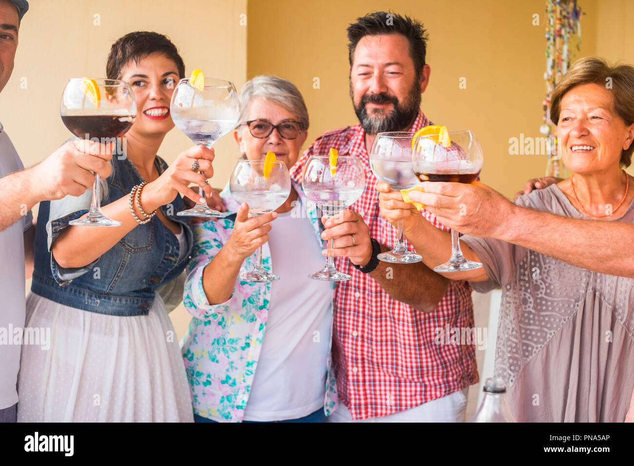 happy group of different ages people celebrating and having fun together in friendship at home or restaurant. cheering and toasting with cocktails and - Stock Image