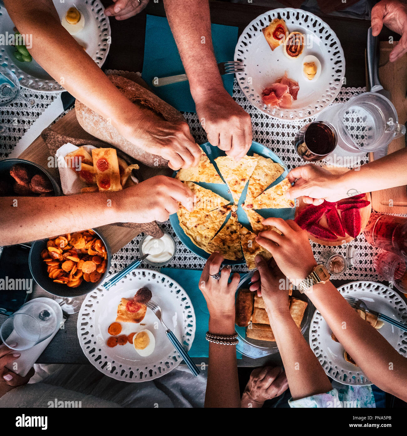 Aerial view from above for table and hands and a lot of food and drinks. celebration and party event concept image. all hands taking from the same pla - Stock Image