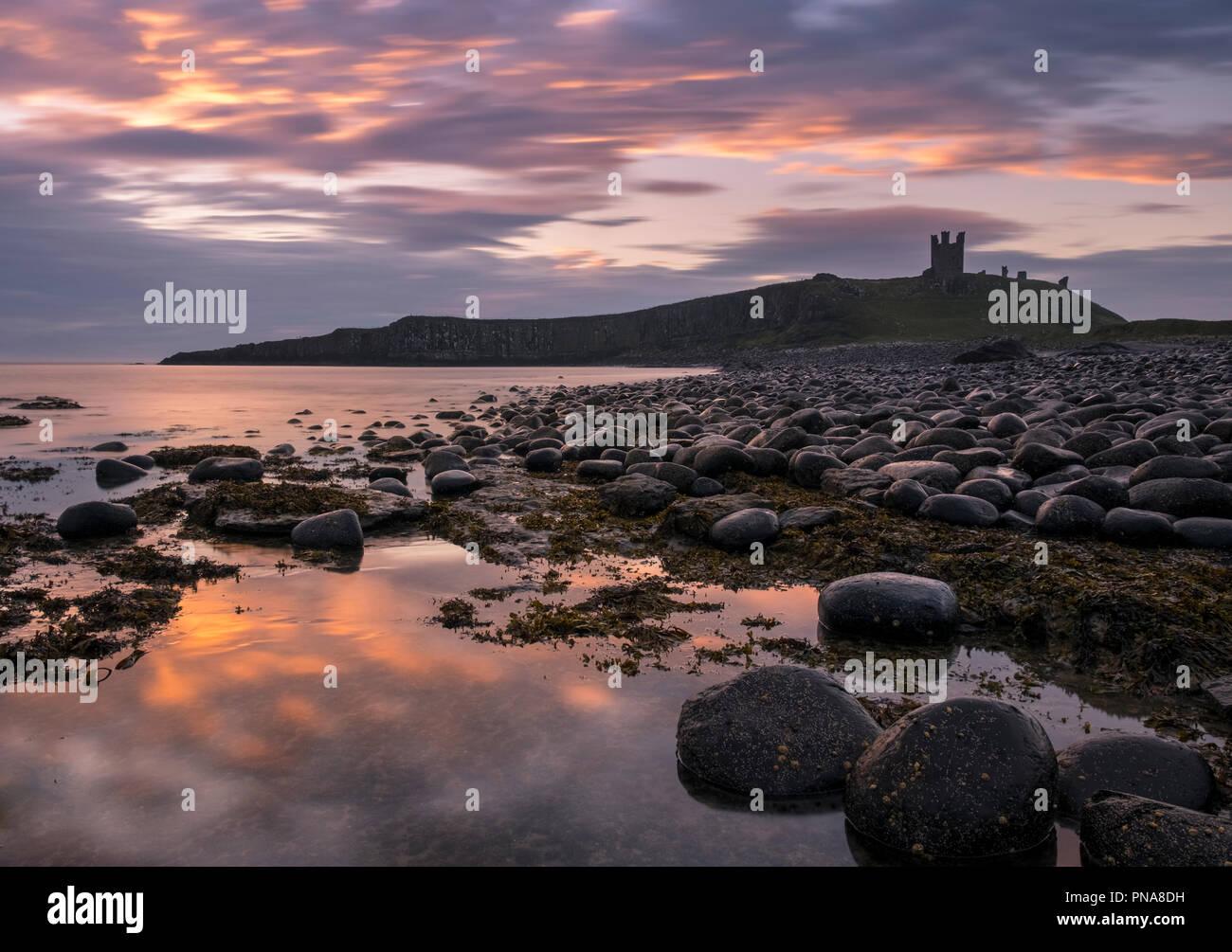 Dunstanburgh Castle at sunrise, Northumberland coast, England, UK Stock Photo