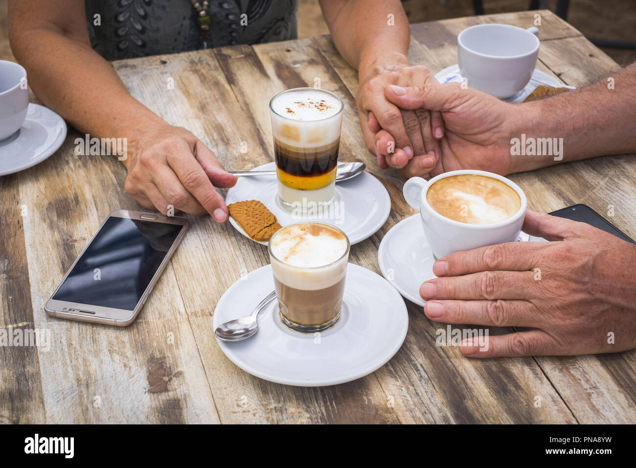 People drinking coffee and cappuccino at the bar over a wooden table with drinks and mobile phone technology. Socializing and love conept for adult ma - Stock Image