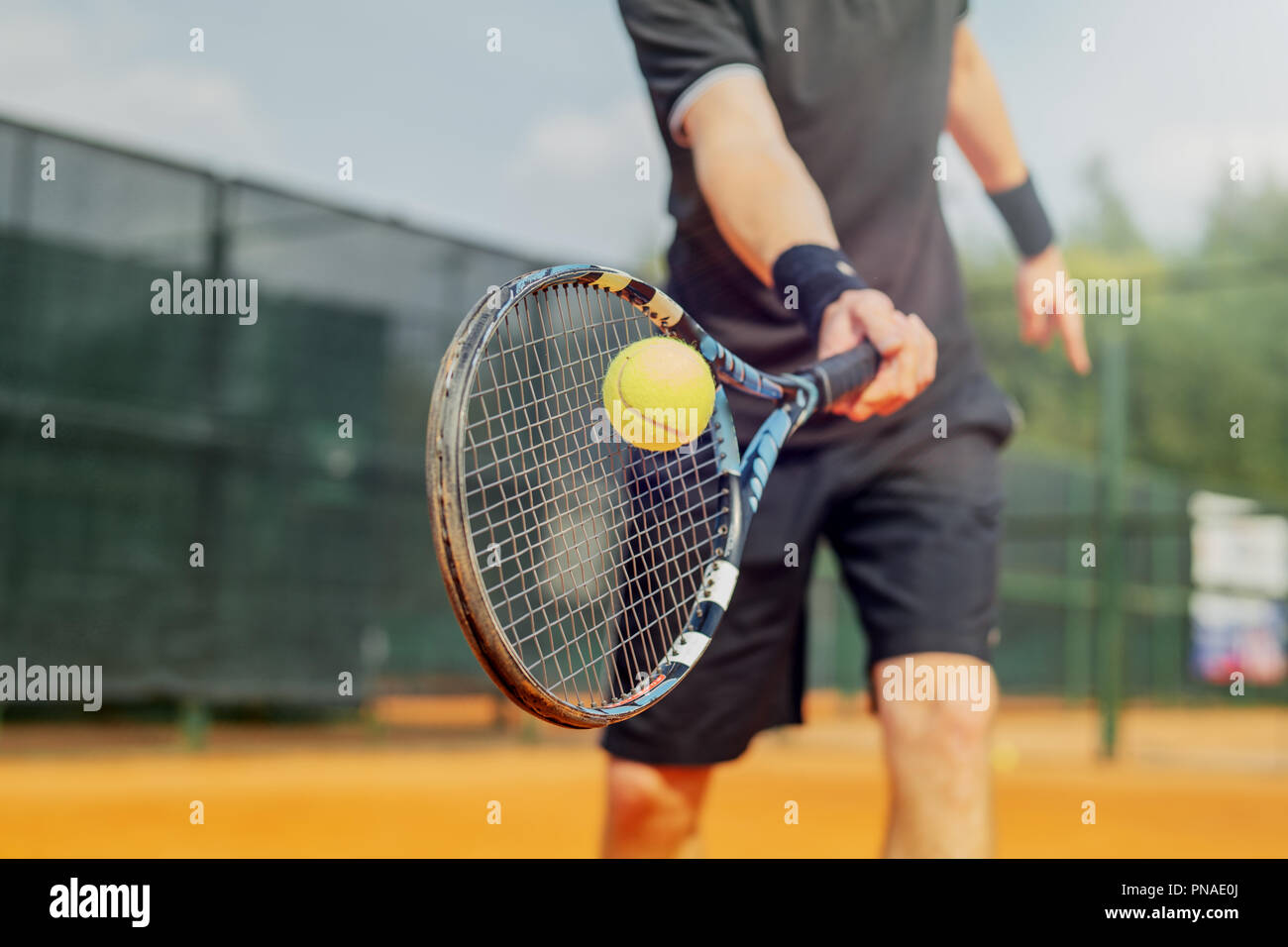 Close up of young attractive man playing tennis at tennis court and beating the ball with a racket. Player is hitting ball with racket while playing m - Stock Image