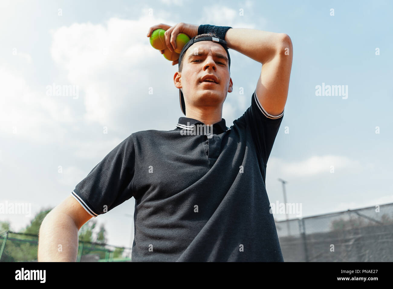 Close up of young attractive man relaxing after tournament and holding tennis balls. Bottom view. Player looking at camera. - Stock Image