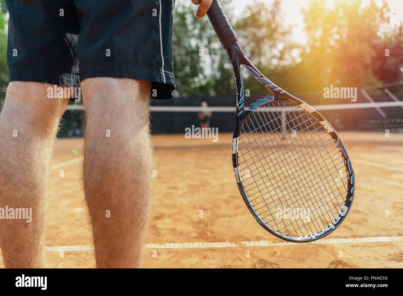 Close up of man holding racket while waiting for ball serving at tennis court. Man is on focus and foreground, tennis net is on background and blurred - Stock Image