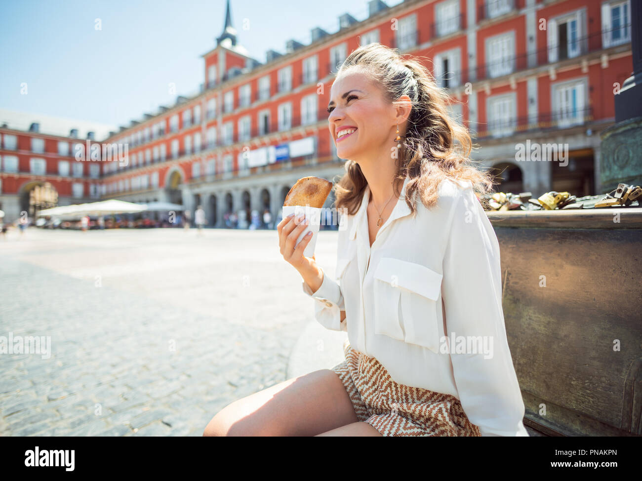 happy young traveller woman with Empanada looking into the distance at Plaza Mayor - Stock Image