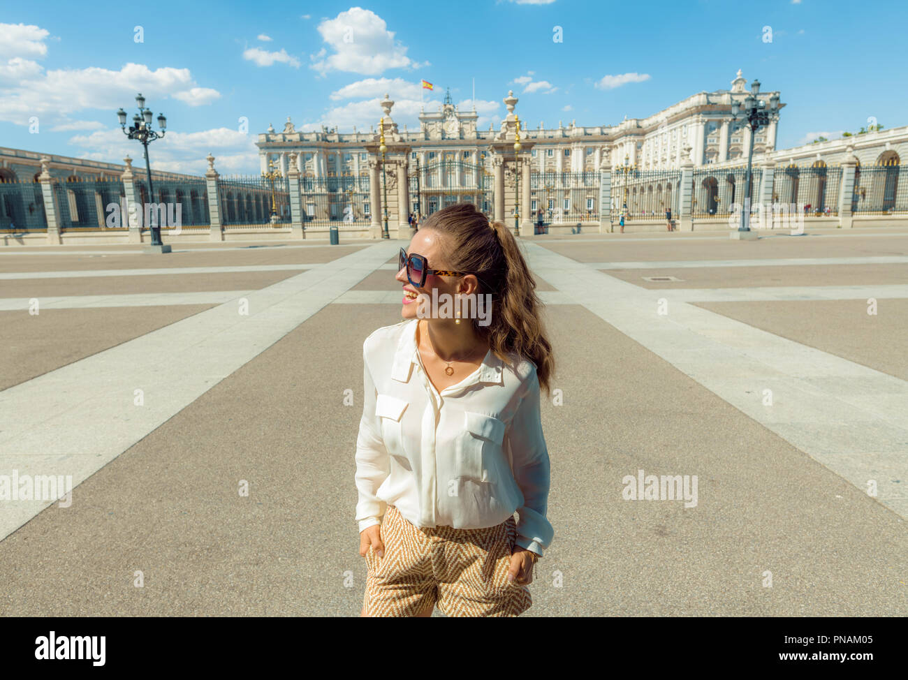 smiling stylish traveller woman near Royal Palace looking into the distance - Stock Image