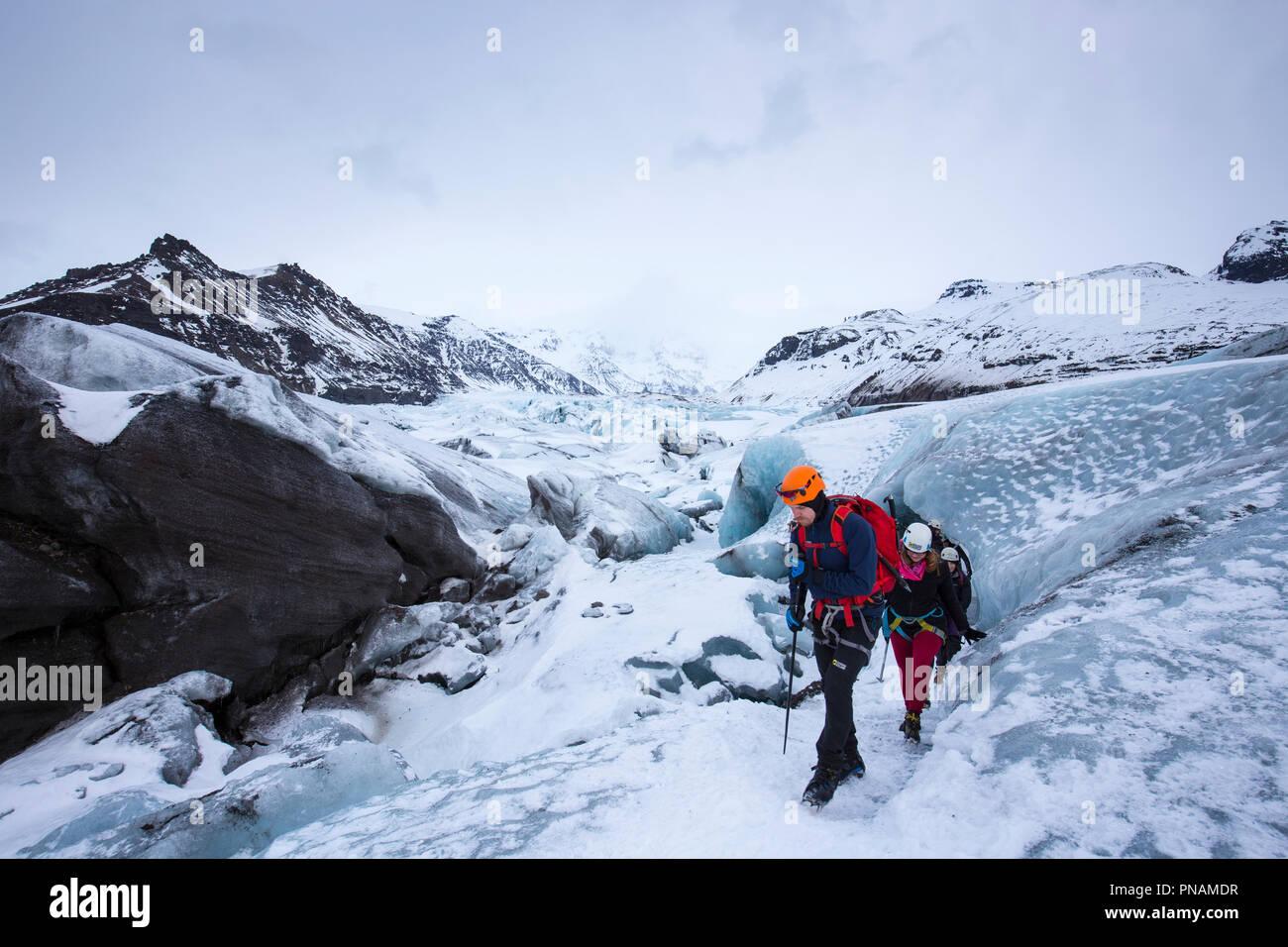 Tourists wearing protective clothing for glacier hike on Svinafellsjokull glacier an outlet glacier of Vatnajokull, South Iceland - Stock Image