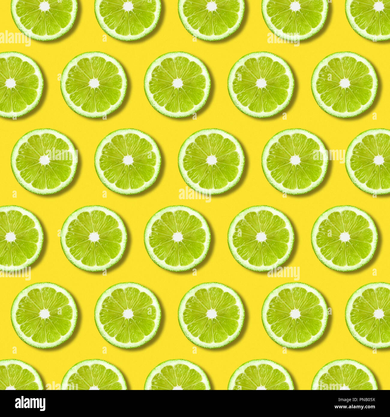 Green lime slices pattern on vibrant yellow color background. Minimal flat lay food texture - Stock Image