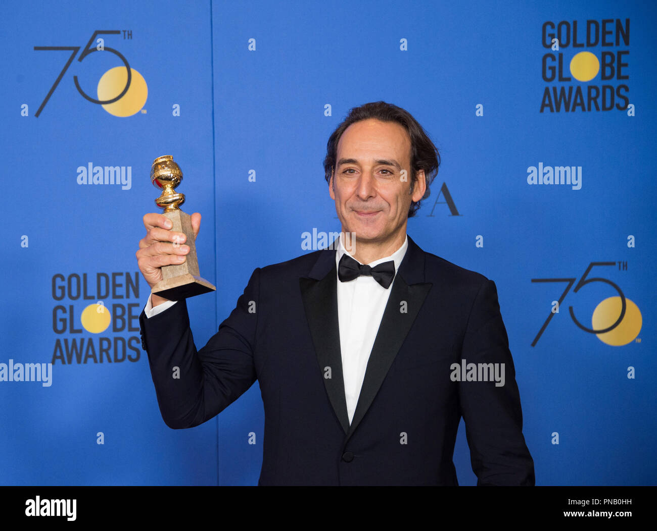 "After winning the category of BEST ORIGINAL SCORE – MOTION PICTURE for ""The Shape of Water,"" Alexandre Desplat poses with the award backstage in the press room at the 75th Annual Golden Globe Awards at the Beverly Hilton in Beverly Hills, CA on Sunday, January 7, 2018. Stock Photo"