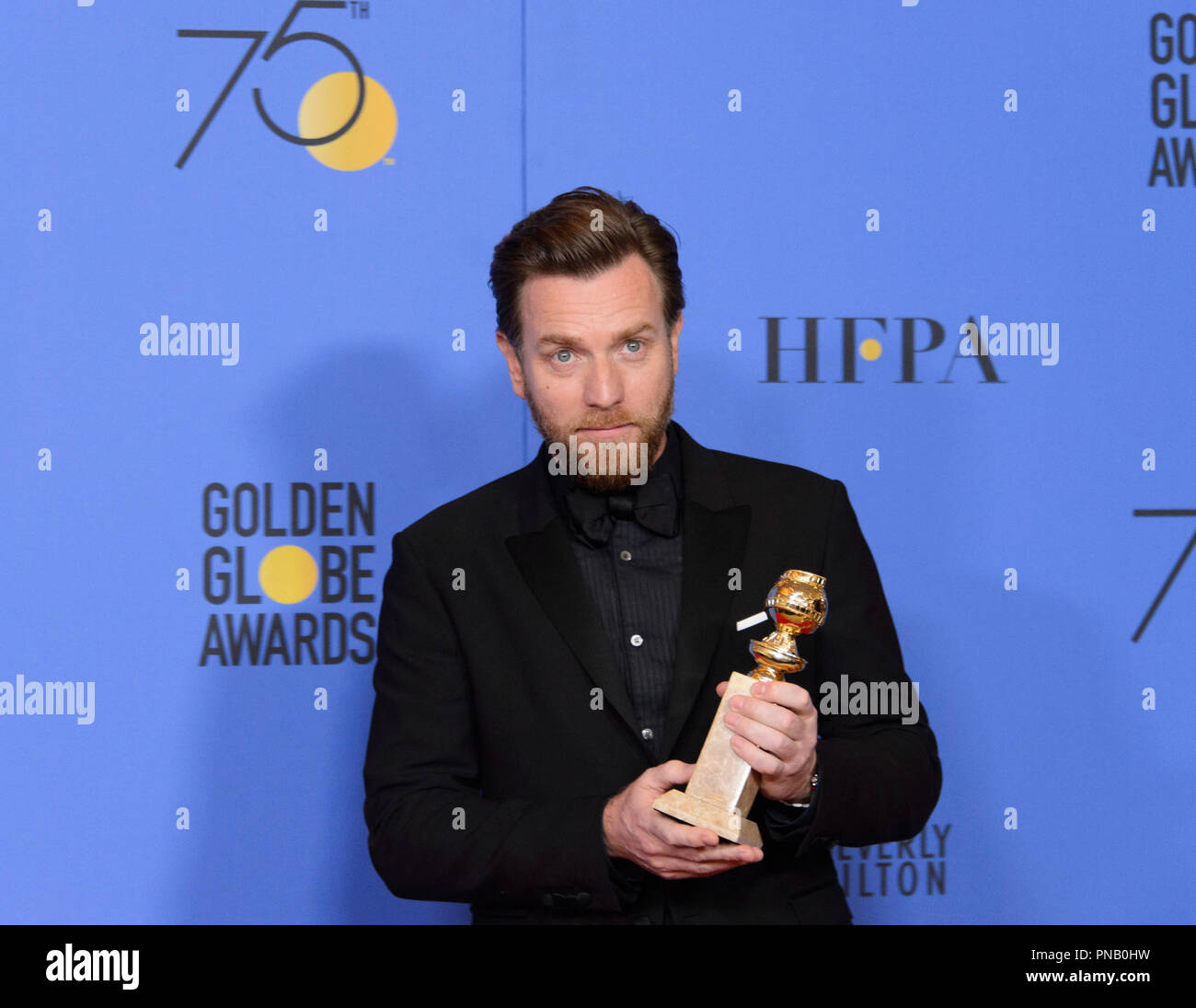 """After winning the category of BEST PERFORMANCE BY AN ACTOR IN A LIMITED SERIES OR A MOTION PICTURE MADE FOR TELEVISION for his role in """"Fargo,"""" actor Ewan McGregor poses backstage in the press room with his Golden Globe Award at the 75th Annual Golden Globe Awards at the Beverly Hilton in Beverly Hills, CA on Sunday, January 7, 2018. Stock Photo"""