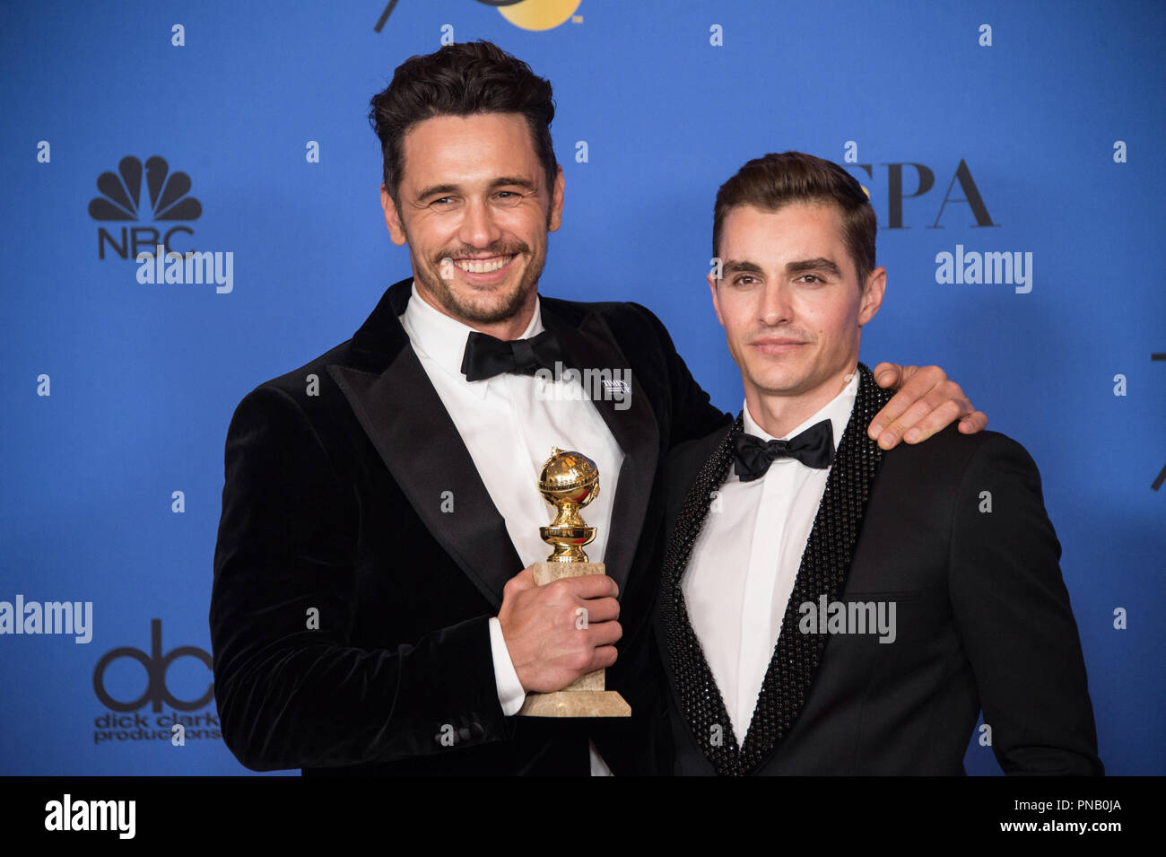 """After winning the category of BEST PERFORMANCE BY AN ACTOR IN A MOTION PICTURE – COMEDY OR MUSICAL for his work in """"The Disaster Artist,"""" actor James Franco poses backstagewith Dave Franco in the press room with his Golden Globe Award at the 75th Annual Golden Globe Awards at the Beverly Hilton in Beverly Hills, CA on Sunday, January 7, 2018. Stock Photo"""