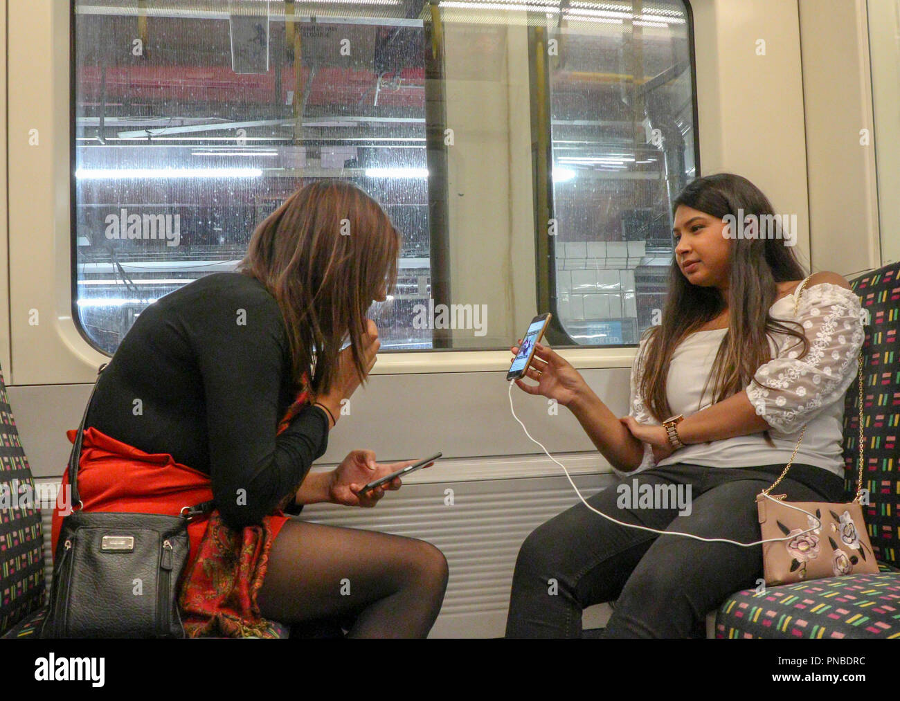 girl on London Underground train showing girlfriend mobile phone screen, England, UK Stock Photo