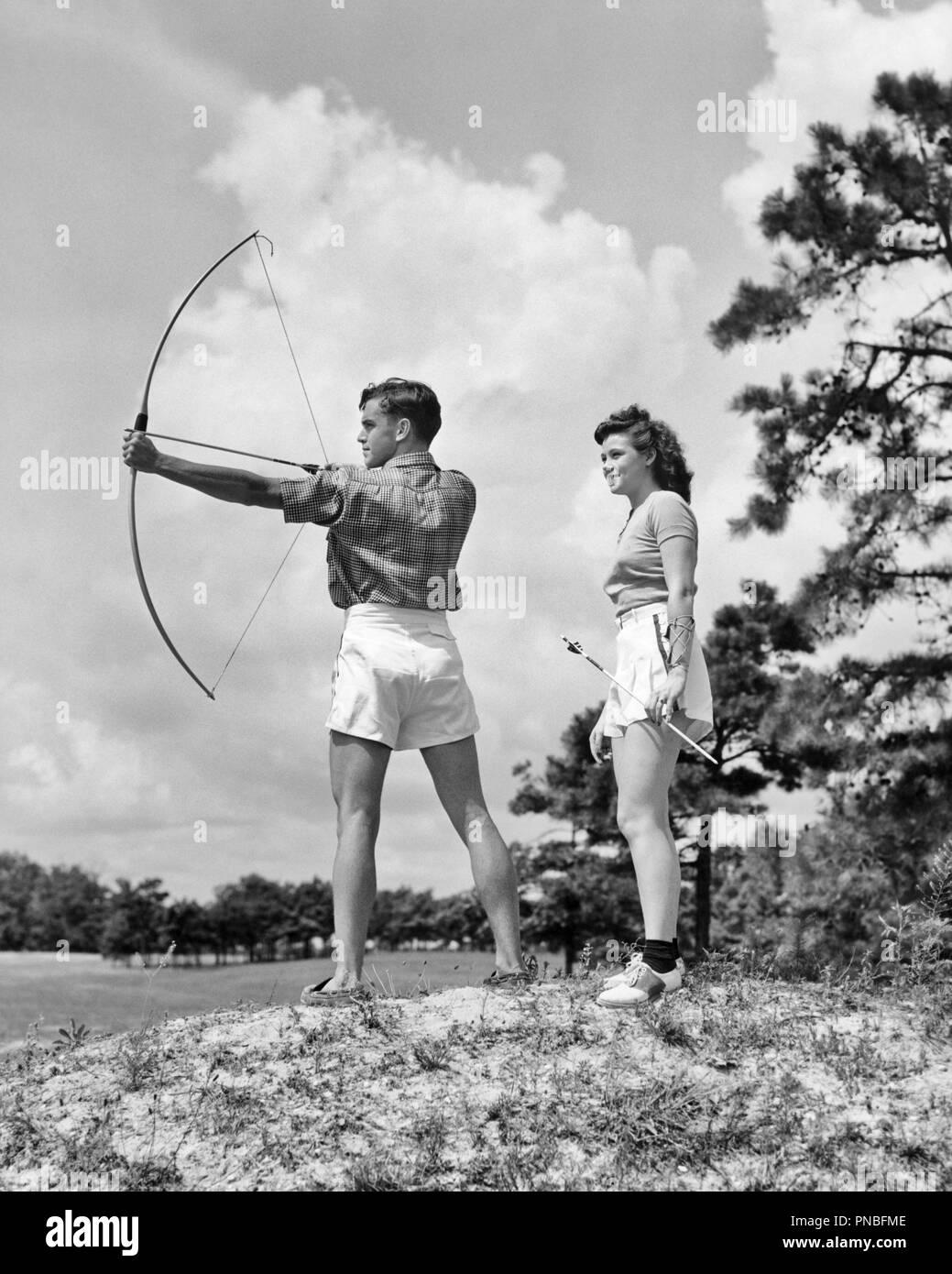 3bd415a1b852 1930s TEENAGE COUPLE PRACTICING ARCHERY SHOOTING BOW AND ARROW - a941  HAR001 HARS JOY LIFESTYLE RURAL