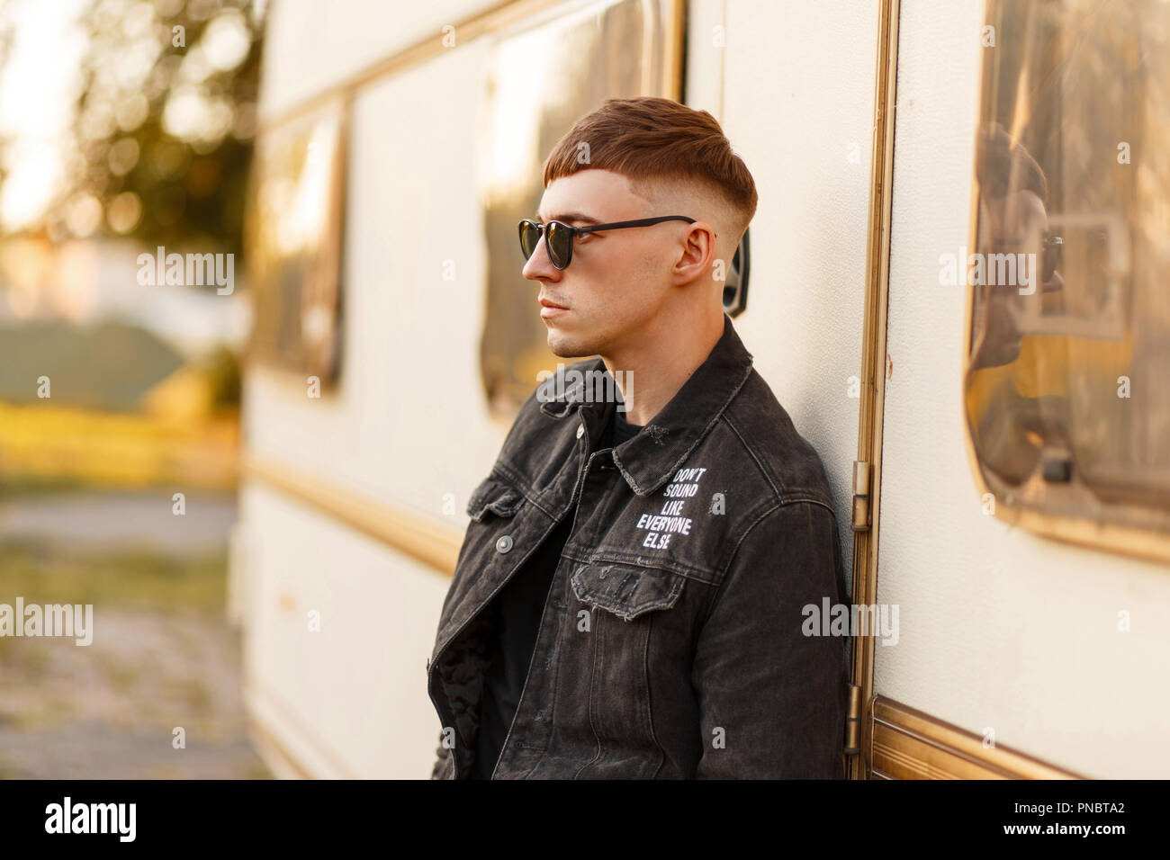 Fashionable Model Man With Sunglasses In A Black Denim Jacket And A