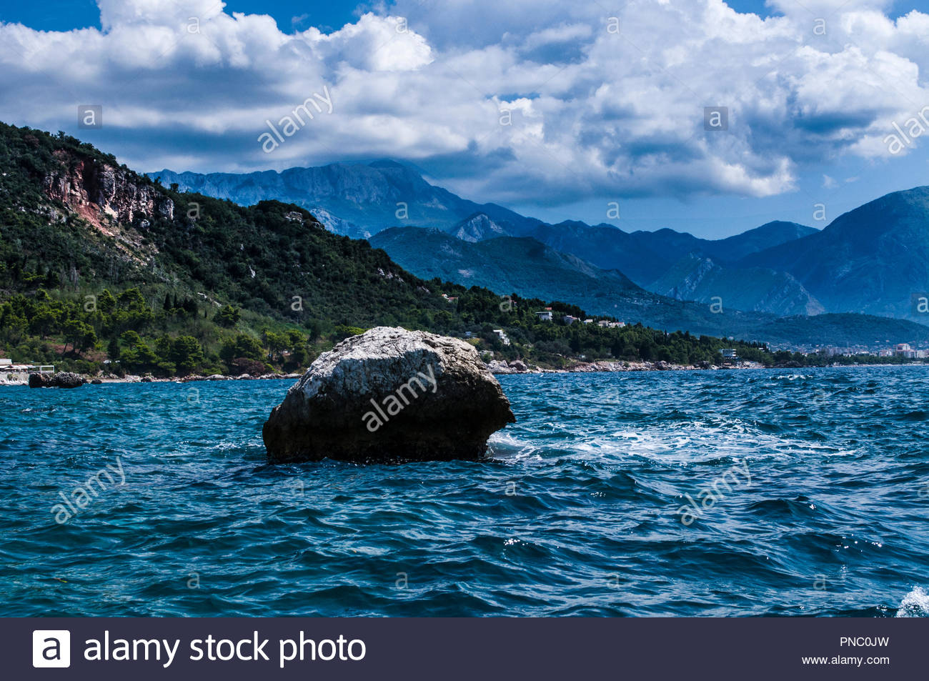 View from the boat, to the city at the foothill of the mountains and the rock - Stock Image