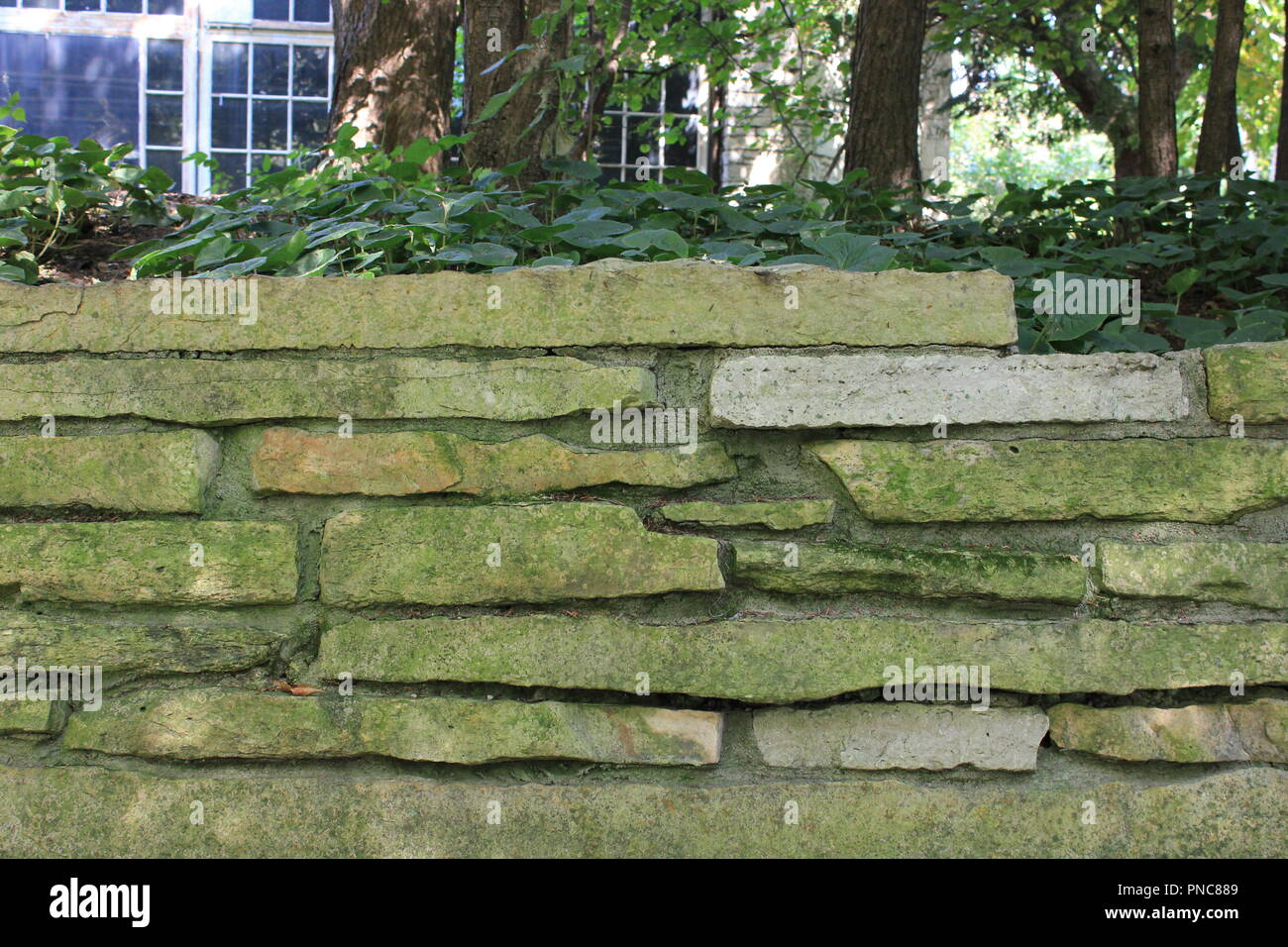 Evanston Historical Society weathered limestone garden wall located on Lake Michigan lakefront property. - Stock Image