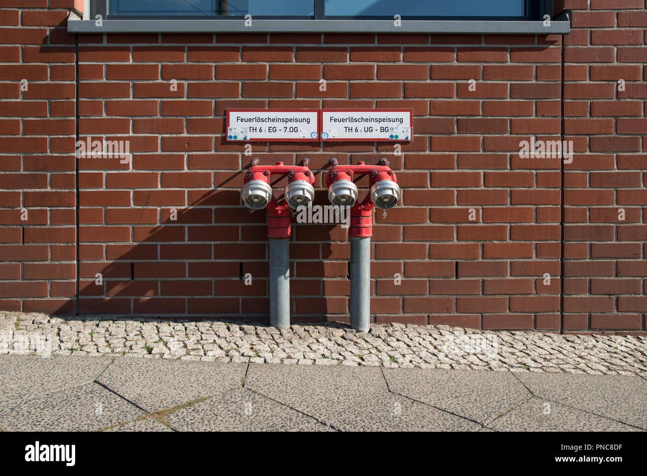 Wasserhydrant an Hauswand auf Berliner Bürgersteig - Stock Image