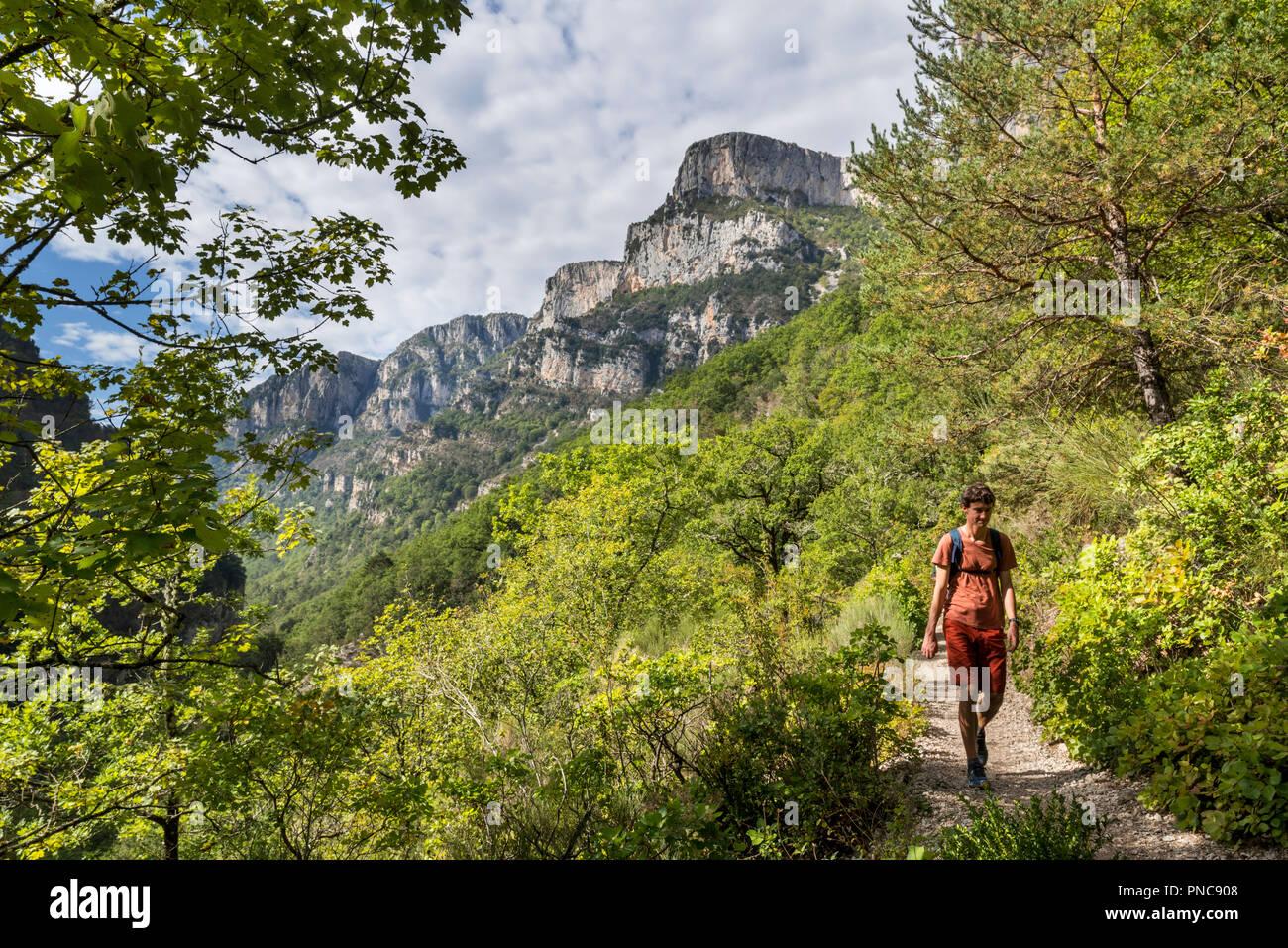 Walker walking along the Sentier Martel path in the Gorges du Verdon / Verdon Gorge canyon, Provence-Alpes-Côte d'Azur, France - Stock Image