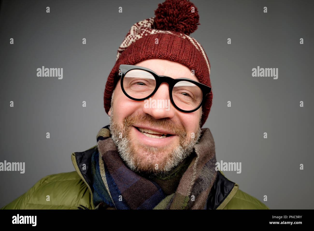 Portrait of mature hipster man in glasses and warm hat posing on gray  background. Smiling bearded man wearing warm clothes for winter studio  shot. Clo c37ea75a97ba