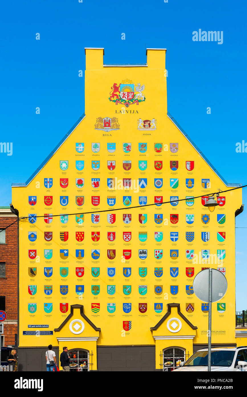Jacob's Barracks, view of the yellow gable end wall of Jacob's Barracks in Old Riga illustrated with the emblems of the cities and towns of Latvia. - Stock Image