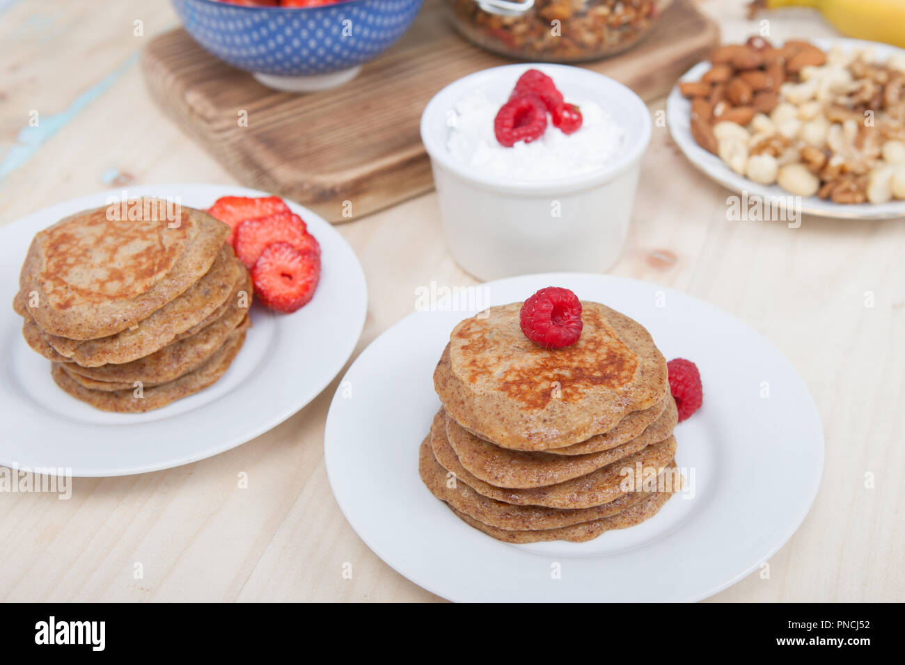 Breakfast: paleo style grain free banana almond pancakes, coconut yogurt with berries, selective focus Stock Photo