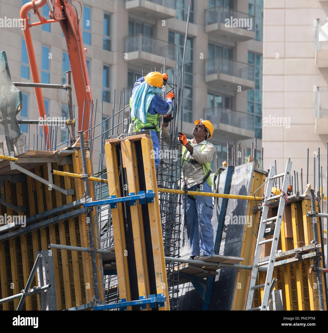Construction workers on site building new high rise luxury apartment building art Downtown Dubai, UAE, united Arab Emirates - Stock Image