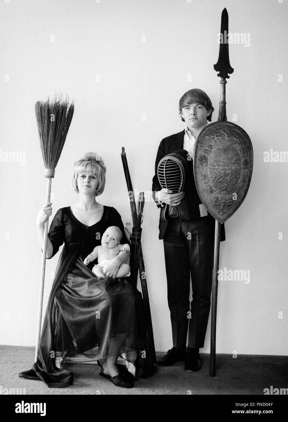1960s PORTRAIT ODD TEEN FAMILY ALL LOOKING AT CAMERA FATHER HOLDING SPEAR SHIELD FENCING MASK MOTHER OLD BROOM AND BABY DAUGHTER - b25460 HAR001 HARS DAD BABIES MOM CLOTHING INDOORS NOSTALGIC PAIR ROMANCE MOTHERS OLD TIME NOSTALGIA OLD FASHION 1 JUVENILE STYLE BLOND YOUNG ADULT COMIC TEAMWORK INFANT MYSTERY ABSTRACT FAMILIES LIFESTYLE FEMALES MARRIED SPOUSE HUSBANDS SHIELD HOME LIFE COPY SPACE FULL-LENGTH LADIES DAUGHTERS PERSONS INSPIRATION BROOM MALES FATHERS B&W EYE CONTACT ODD WEIRD ADVENTURE STRANGE AND DADS ZANY UNCONVENTIONAL CONNECTION CONCEPTUAL IMAGINATION STYLISH TEENAGED UNUSUAL - Stock Image