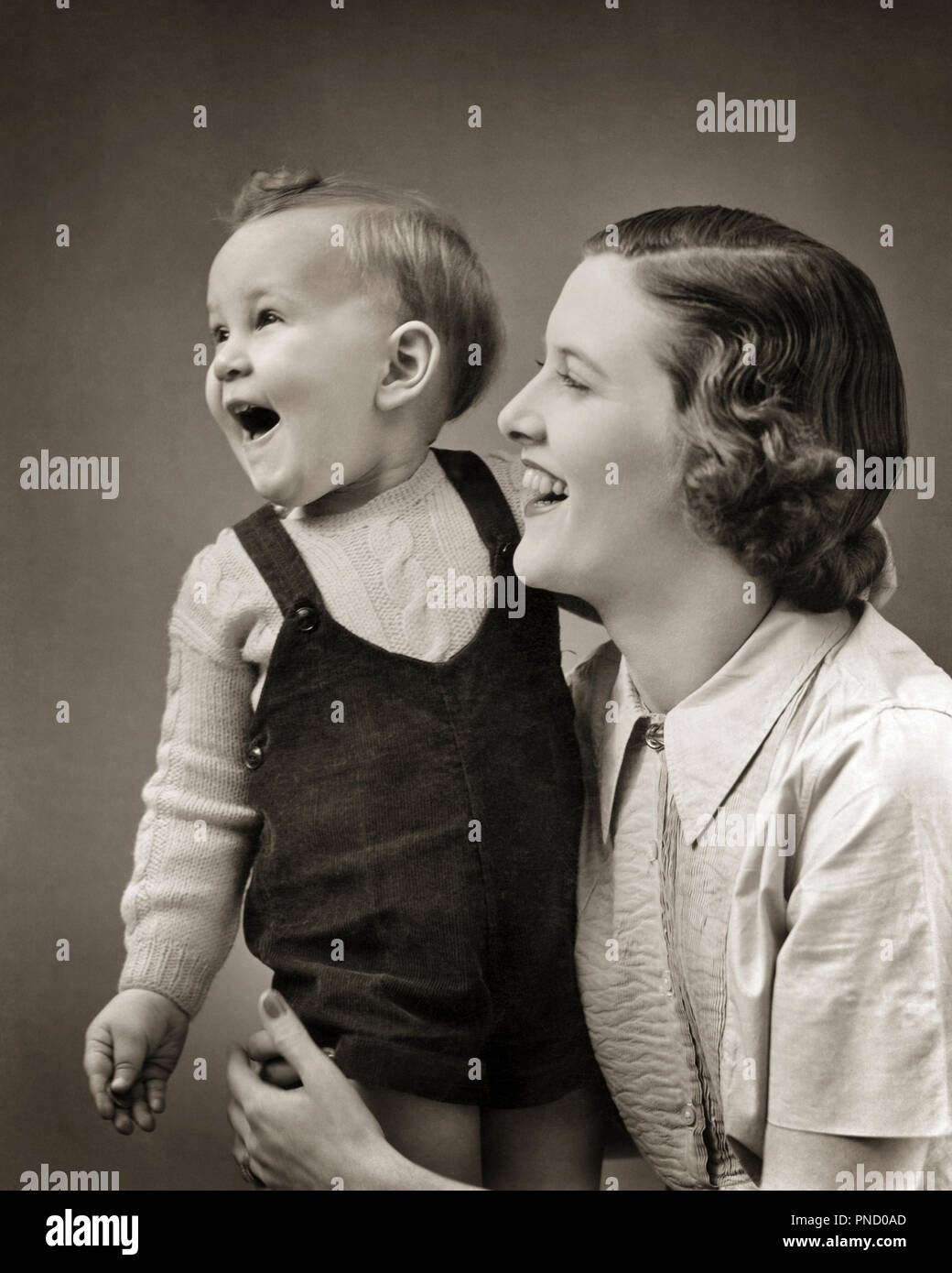 1940s LAUGHING BABY BOY TODDLER STANDING SUPPORTED BY