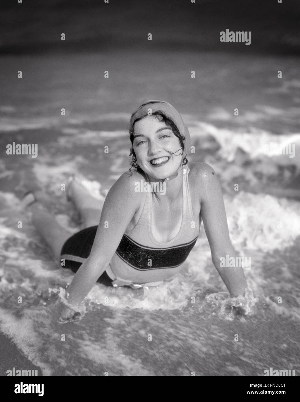 1920s SMILING BRUNETTE WOMAN LYING IN BEACH SURF WAVES WEARING BATHING CAP SWIMSUIT LOOKING AT CAMERA - b5831 HAR001 HARS LADIES PERSONS SURF B&W EYE CONTACT BRUNETTE SHORE HAPPINESS CHEERFUL HIGH ANGLE STYLES EXCITEMENT RECREATION BEACHES SMILES JOYFUL STYLISH BATHING SUIT FASHIONS SEASHORE YOUNG ADULT WOMAN BLACK AND WHITE CAUCASIAN ETHNICITY COASTAL HAR001 OLD FASHIONED - Stock Image