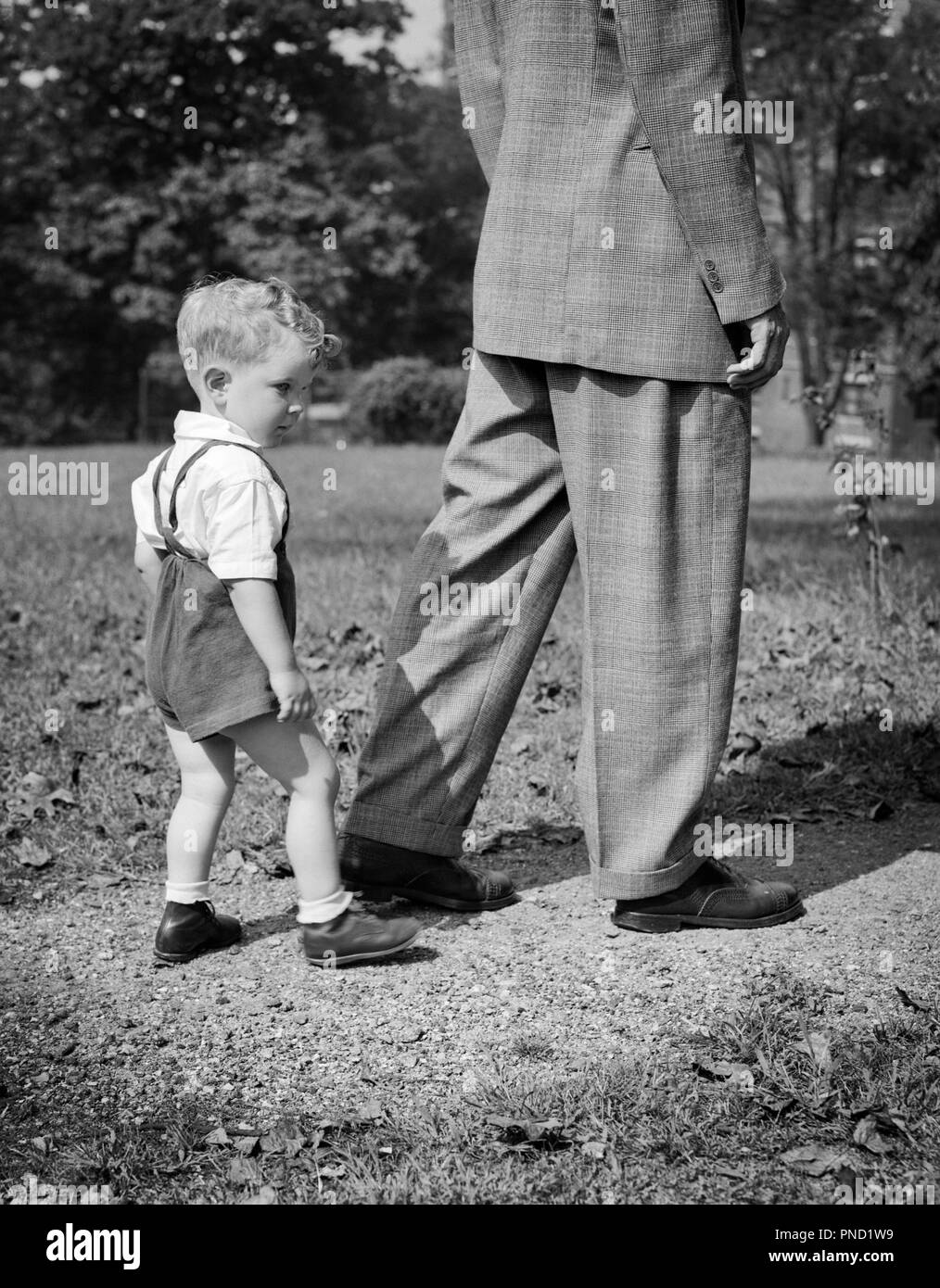 1940s BOY FOLLOWING BEHIND MAN WALKING IN HIS FATHER'S FOOTSTEPS - j10745 HAR001 HARS COPY SPACE FULL-LENGTH PERSONS INSPIRATION MALES FATHERS B&W SUCCESS MENTOR HIS STYLES DADS LEADERSHIP PROGRESS FATHER AND SON DIRECTION PRIDE REAR VIEW FOLLOWING GENERATION FATHER'S CONNECTION CONCEPTUAL EXAMPLE FOLLOW FOOTSTEPS LEAD LEGACY STYLISH BABY BOY BACK VIEW FASHIONS GROWTH JUVENILES MID-ADULT MID-ADULT MAN TOGETHERNESS BLACK AND WHITE HAR001 OLD FASHIONED - Stock Image