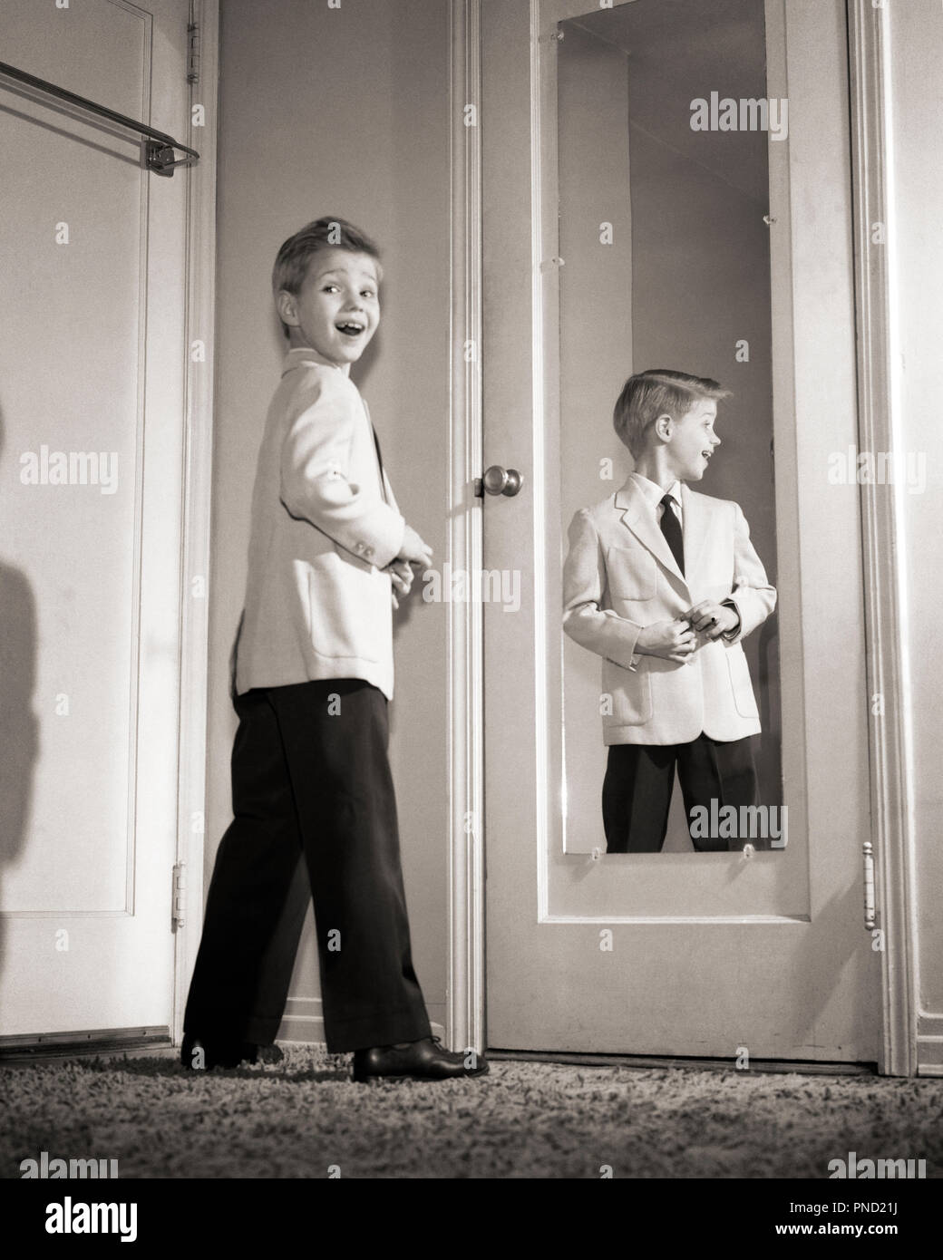 1950s SMILING PRE-TEEN BOY YOUNG MAN WEARING SPORTS JACKET AND TIE STANDING BEFORE MIRROR LOOKING AT CAMERA BACK OVER SHOULDER - j2457 DEB001 HARS MALES CONFIDENCE B&W EYE CONTACT SUCCESS VISION SUIT AND TIE BEFORE HAPPINESS CHEERFUL STYLES AND YOUNG MAN EXCITEMENT LOOKING BACK PRIDE SMILES SPORTS JACKET STEPPING OUT JOYFUL STYLISH DEB001 DRESSED UP FASHIONS JUVENILES PRE-TEEN PRE-TEEN BOY BLACK AND WHITE CAUCASIAN ETHNICITY OLD FASHIONED - Stock Image